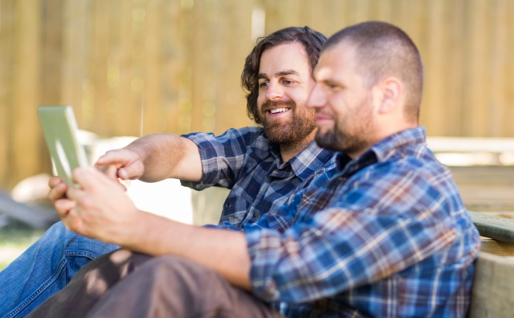 Carpenter Holding Digital Tablet While Coworker Pointing At It
